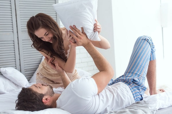Couple Playfully Pillow Fighting