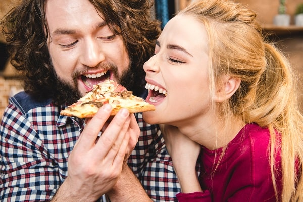 Lighthearted Couple Happily Sharing a Slice of Pizza